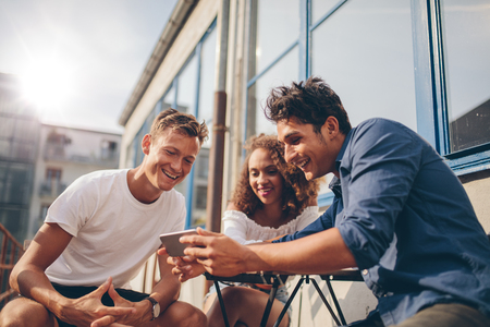 Foto de Three young friends sitting outdoors and looking at mobile phone. Group of people sitting at outdoor cafe and watching video on the smartphone. - Imagen libre de derechos