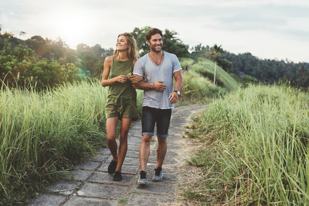 Photo pour Outdoor shot of young couple in love walking on pathway through grass field. Man and woman walking along tall grass field. - image libre de droit