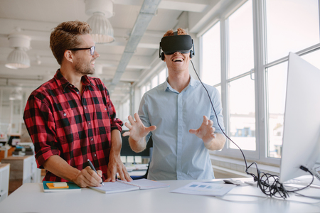 Photo for Shot of two young men testing virtual reality glasses in office. Businessman wearing VR goggles and colleague writing notes. - Royalty Free Image