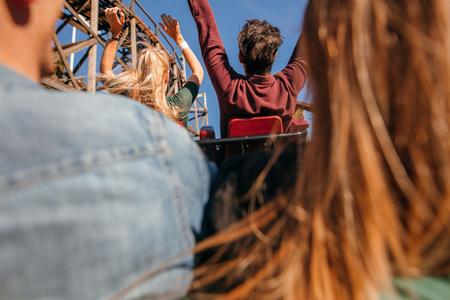 Photo pour Rear view shot of young friends riding roller coaster ride at amusement park. - image libre de droit