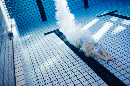 Photo pour Underwater shot of female swimmer swimming inside pool. Fit young female swimmer training in the pool. - image libre de droit