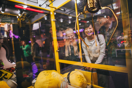 Photo pour Happy young woman playing toy grabbing game with friends at amusement park. - image libre de droit