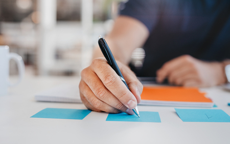 Photo for Close up image of business man writing on an adhesive note at table in office, focus on hand and pen. - Royalty Free Image