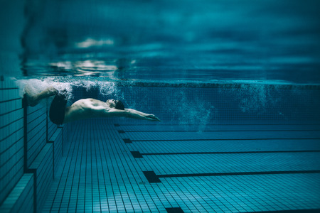 Photo for Underwater shot of male swimmer turning over in swimming pool. Pro male swimmer in action inside pool. - Royalty Free Image