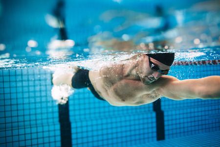 Photo pour Underwater shot of professional male athlete swimming in pool. Man swimmer in action. - image libre de droit
