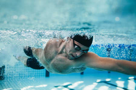 Photo for Underwater shot of fit swimmer training in the pool. Professional male swimmer inside swimming pool. - Royalty Free Image