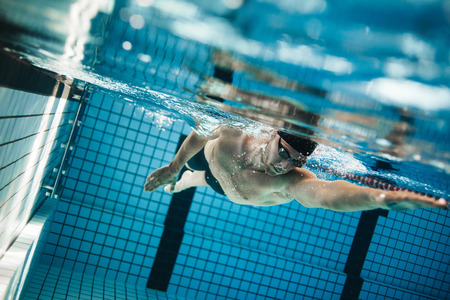Photo pour Underwater shot of professional male athlete swimming in pool. Young man swimming the front crawl in a pool. - image libre de droit