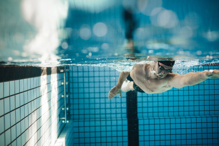 Photo pour Fit young male swimmer training in the pool. Pro male swimmer in action inside swimming pool. - image libre de droit