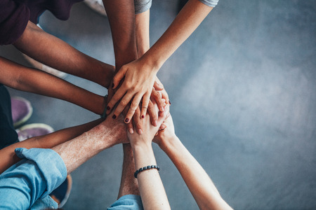 Photo for Close up top view of young people putting their hands together. Friends with stack of hands showing unity and teamwork. - Royalty Free Image