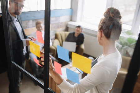 Photo for Business people having a meeting in office. Woman standing in front of glass wall with post it notes and explaining business ideas to colleagues. - Royalty Free Image