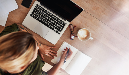 Foto de Top view shot of woman sitting at table with laptop and coffee writing on notebook. Female making to do list on diary. - Imagen libre de derechos