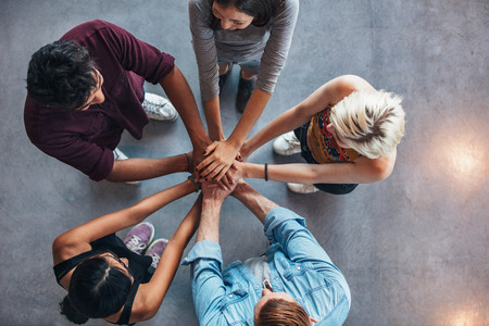 Foto de Top view of young people with hands on top of each other. Young students making a stack of hands. - Imagen libre de derechos