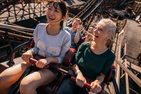Photo for Shot of smiling young people riding a roller coaster. Young women and men having fun on amusement park ride. - Royalty Free Image