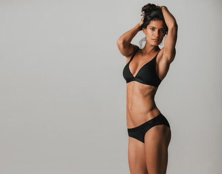 Photo for Sexy shapely young woman with a healthy toned body posing in black lingerie with her arms raised to her long hair, three quarter over grey with copy space - Royalty Free Image