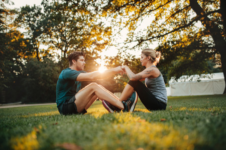 Photo for Young couple cooperating while stretching at park. Man and woman sitting together holding hands and exercising. - Royalty Free Image