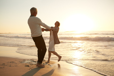 Photo pour Full length shot of romantic senior couple enjoying a day at the beach. Mature couple enjoying their vacation on the beach. - image libre de droit