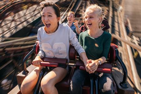 Foto de Shot of happy young people riding a roller coaster. Young women and men having fun on amusement park ride. - Imagen libre de derechos