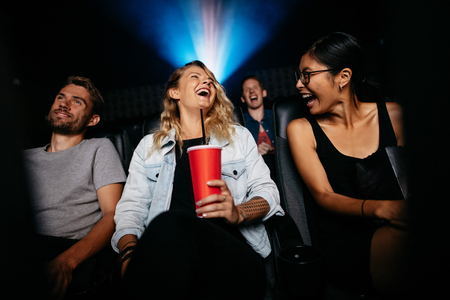 Photo for Young woman with friends in cinema hall watching movie. Group of people watching movie in theater and laughing. - Royalty Free Image