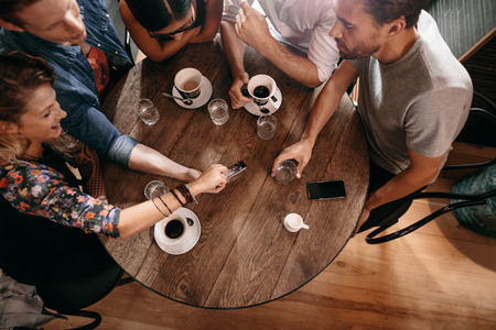 Photo for Top view of young people sitting around a cafe table and looking at mobile phone. Young men and women looking at pictures on smart phone. - Royalty Free Image