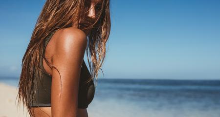 Foto de Close up shot of sensuous young woman on the beach. Young caucasian female model posing on the sea shore with copy space. - Imagen libre de derechos