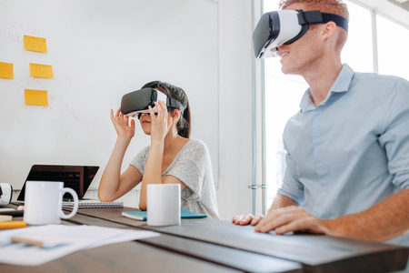 Foto de Young man and woman sitting at a table and using virtual reality goggles. Business team using virtual reality headset in office meeting. - Imagen libre de derechos