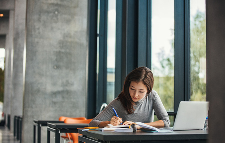Photo pour Shot of young asian female student sitting at table and writing on notebook. Young female student studying in library. - image libre de droit