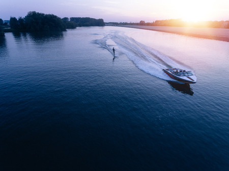 Photo pour Aerial view of man wakeboarding on lake at sunset. Water skiing on lake behind a boat. - image libre de droit