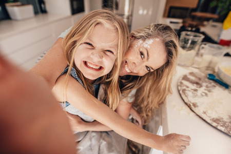 Photo for Smiling little girl and woman in kitchen taking selfie. Happy young mother and daughter cooking food. - Royalty Free Image