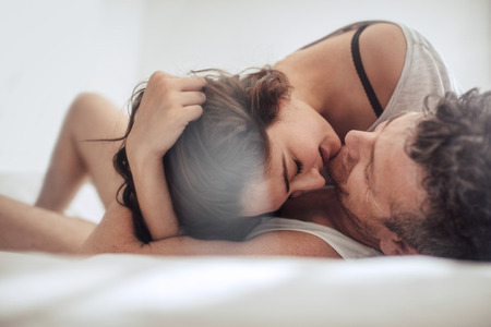 Photo pour Young couple caressing in bed together. Romantic couple in a relationship enjoying on bed. - image libre de droit