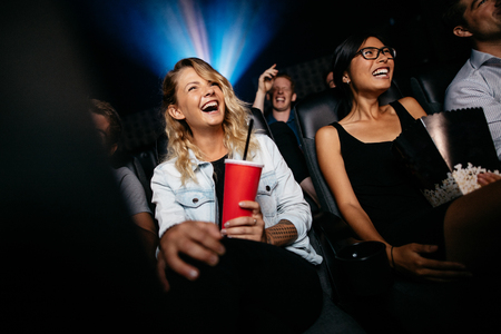 Photo for Young people laughing while watching film in movie theater. Group of friends in multiplex cinema with drinking and popcorn. - Royalty Free Image