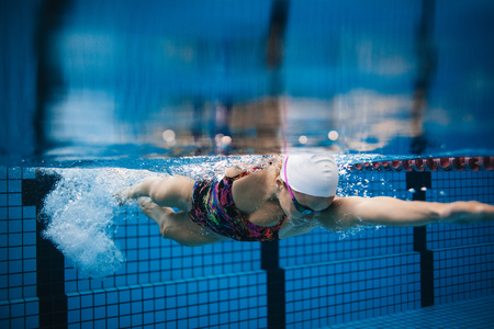 Photo pour Underwater shot of young sportswoman swimming in pool. Female swimmer in action inside swimming pool. - image libre de droit