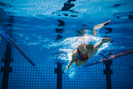 Photo pour Underwater shot of woman training in swimming pool. Female swimmer in action inside swimming pool. - image libre de droit