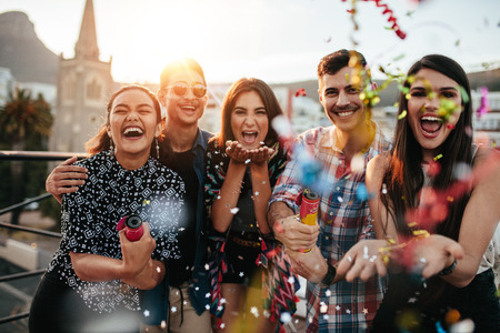 Foto per Group of friends enjoying party and throwing confetti. Friends having fun at rooftop party. - Immagine Royalty Free