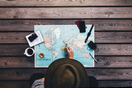 Foto de Tourist pointing at Europe on world map surrounded with binoculars, compass and other travel accessories. Man wearing brown hat planning his tour looking at the world map. - Imagen libre de derechos