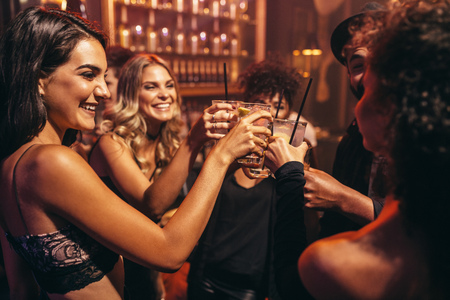 Foto de Group of young people with cocktails at nightclub. Best friends partying in a pub and toasting drinks. - Imagen libre de derechos