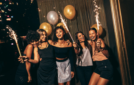 Photo pour Group of women celebrating with fireworks at pub. Female friends enjoying party at nightclub. - image libre de droit