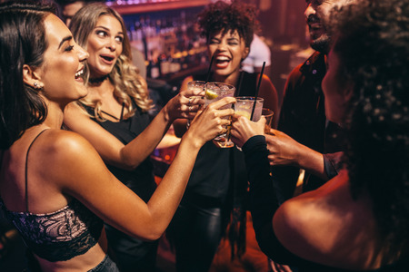 Photo for Group of friends partying in a nightclub and toasting drinks. Happy young people with cocktails at pub. - Royalty Free Image
