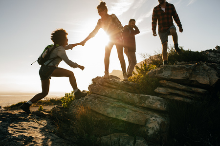 Foto de Group of hikers on a mountain. Woman helping her friend to climb a rock. Young people on mountain hike at sunset. - Imagen libre de derechos