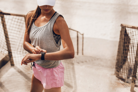 Photo pour Young woman setting fitness app before workout. Female runner using smart watch to monitor her performance. - image libre de droit