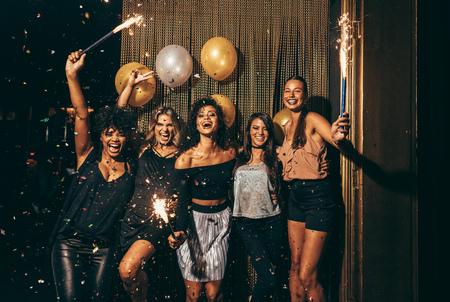 Foto de Shot best friends celebrating new year's eve holding sparklers in a party. Group of women having party at nightclub. - Imagen libre de derechos