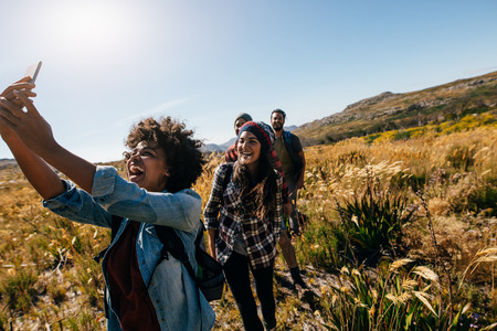 Photo for Happy young woman taking pictures of friends while hiking. Group of friends on country walk taking selfie. - Royalty Free Image