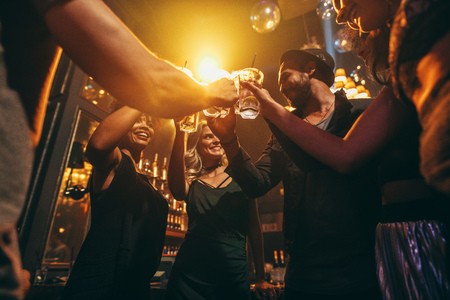 Foto de Low angle shot of group of friends enjoying drinks at bar together. Young people at nightclub toasting cocktails. - Imagen libre de derechos