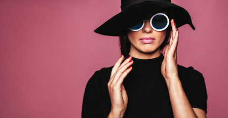 Photo pour Close up portrait of stylish caucasian female model. Woman in hat and sunglasses posing over pink background. - image libre de droit