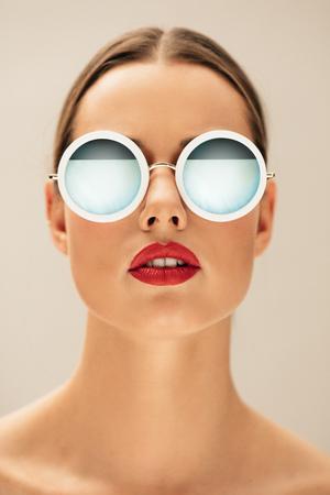 Photo pour Close up vertical portrait of young woman wearing sunglasses. Caucasian female model posing against beige background. - image libre de droit