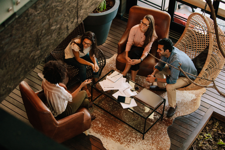 Foto de Top view of four business colleagues sitting on office lobby and discussing new ideas. Corporate business team meeting in office. - Imagen libre de derechos