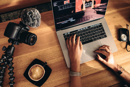 Foto de Top view of female vlogger editing video on laptop. Young woman working on computer with coffee and cameras on table. - Imagen libre de derechos