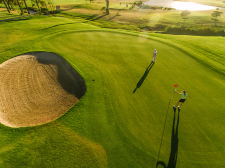 Photo for Golf course top view with players. Aerial view of golfers on putting green. - Royalty Free Image