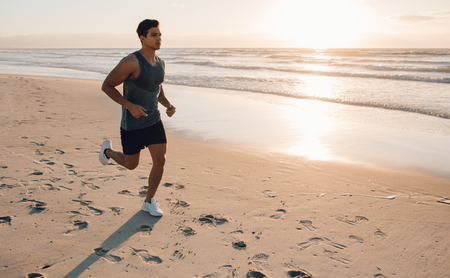 Photo for Young man on morning run outdoors on sea shore. Young man training on the beach in morning. - Royalty Free Image