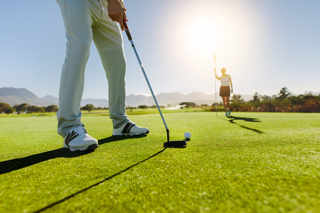 Foto de Low angle view of golfer on putting green about to take the shot. Male golf player putting on green with second female player in the background holding the flag. - Imagen libre de derechos
