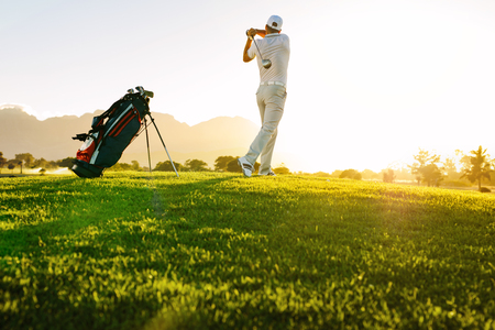 Foto de Low angle shot of professional golfer taking shot while standing on field. Full length of golf player swinging golf club on sunny day. - Imagen libre de derechos